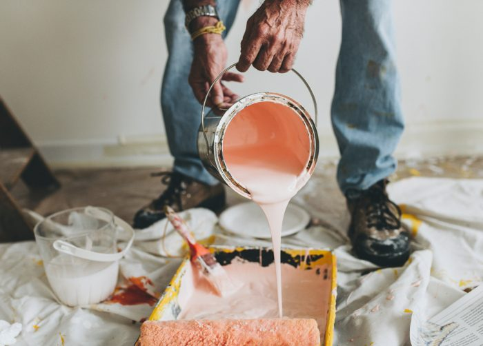 Light pink paint being poured into a container with paint roller