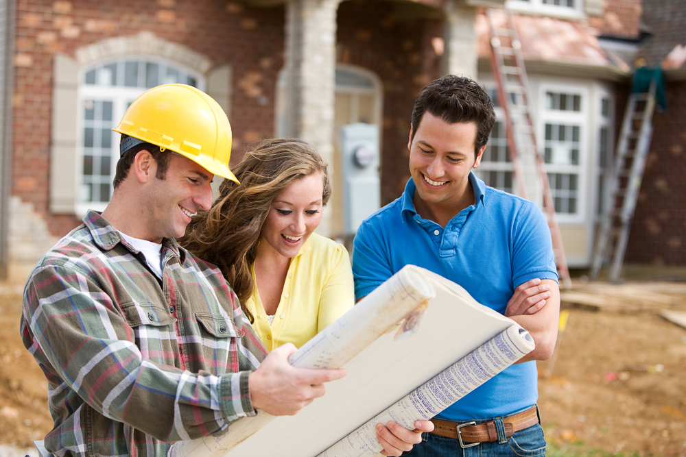A young couple going over blue prints with their builder