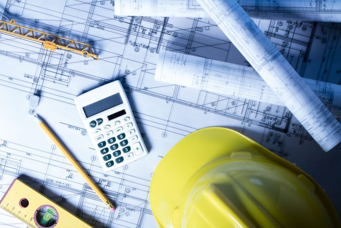 A blue print with a yellow construction hat, calculator, pencil and level on top